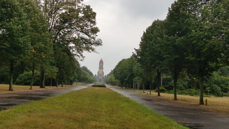 Bäume und Wiese umrahmen eine Allee, im Hintergrund ein historisches Friedhofsgebäude auf dem Leipziger Südfriedhof.