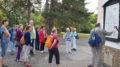 Menschen auf Kiesweg vor Bäumen, vor einem Mann, der spricht.