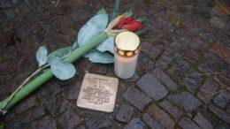 Stolperstein, mit Kerze und Blume.