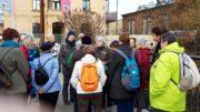 Eine Gruppe Wanderer steht auf einer Brücke und folgt den Erklärungen der Gruppenleiterin.
