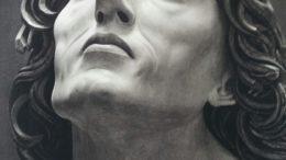 Kopf einer Engelsskulptur aus Stein gen Himmel blickend.