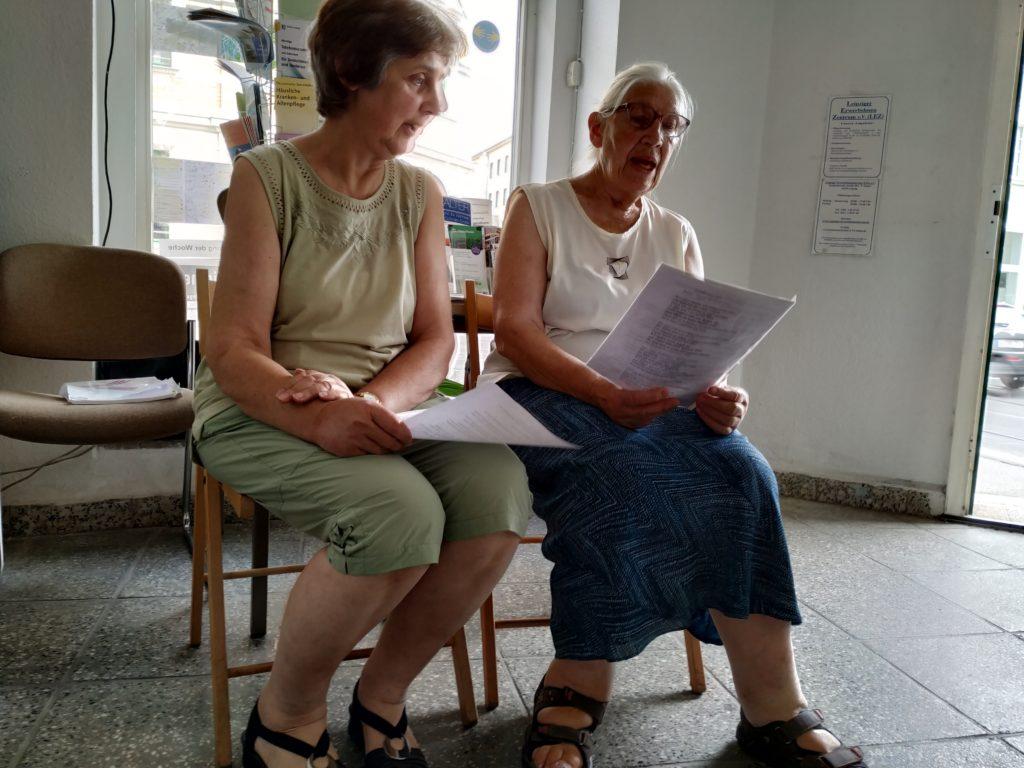 Zwei Frauen sitzend, eine Theaterszene probend.