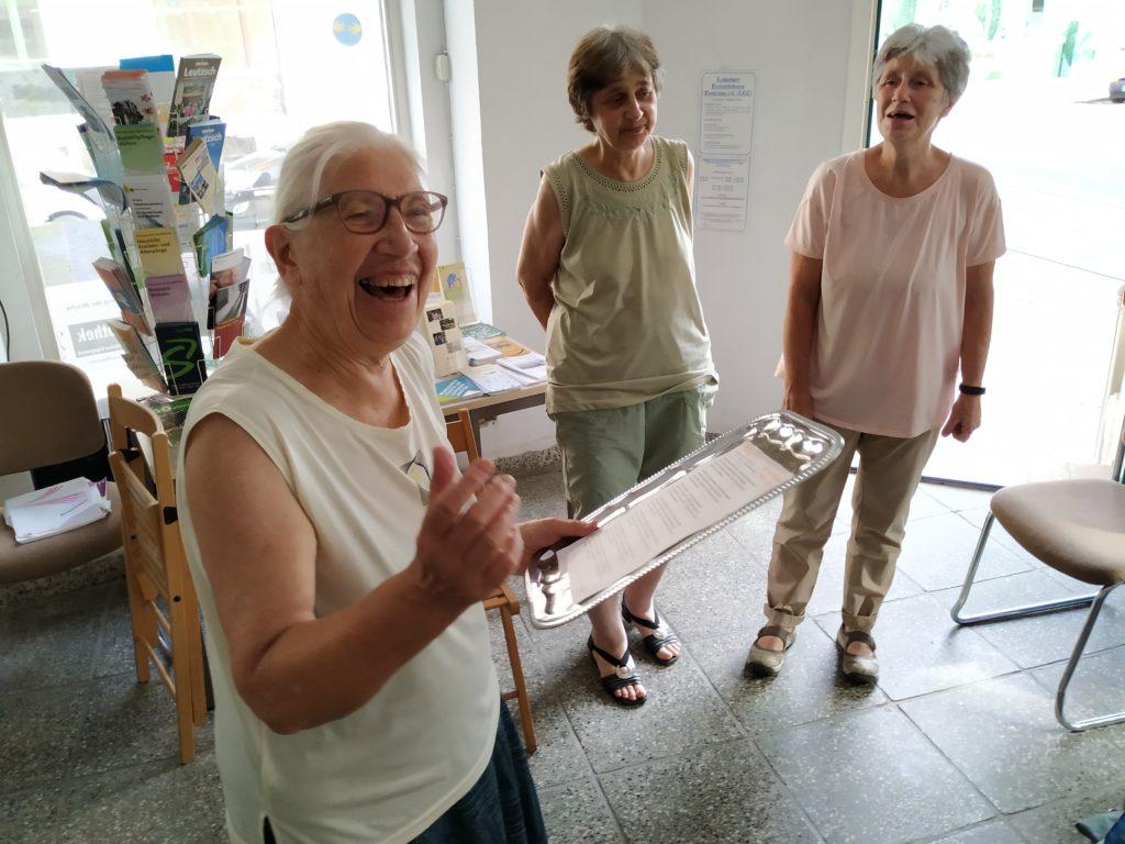Eine Frau singt ein Lied im Stadtteilladen Leutzsch, zwei andere im Hintergrund singen den Refrain.