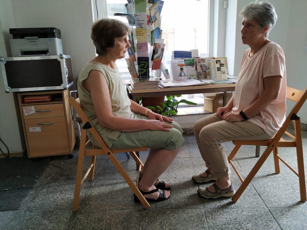 Zwei Frauen sitzen sich auf Stühlen gegenüber und proben eine Szene.