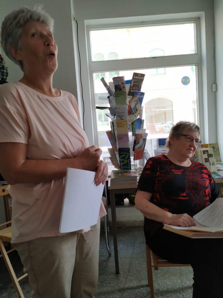 Zwei Frauen, eine stehend, die andere auf einem Stuhl sitzend mit Buch, sind bei einer Kabarettprobe zu sehen.
