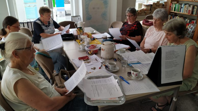 Eine Gruppe von Frauen sitzt singend um einen Tisch herum.