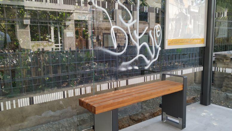Weißes Graffiti auf der Glasrückwand des neuen Haltestellenhäuschens am Rathaus Leutzsch.