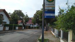 Bushatestellenschild an Straße mit Bäumen und Häusern.