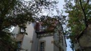 Oberer Teil einer Villa von Bäumen eingerahmt.