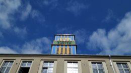 Blau-gelber Turm mit grünem Schild auf saniertem Haus vor blauem Himmel.