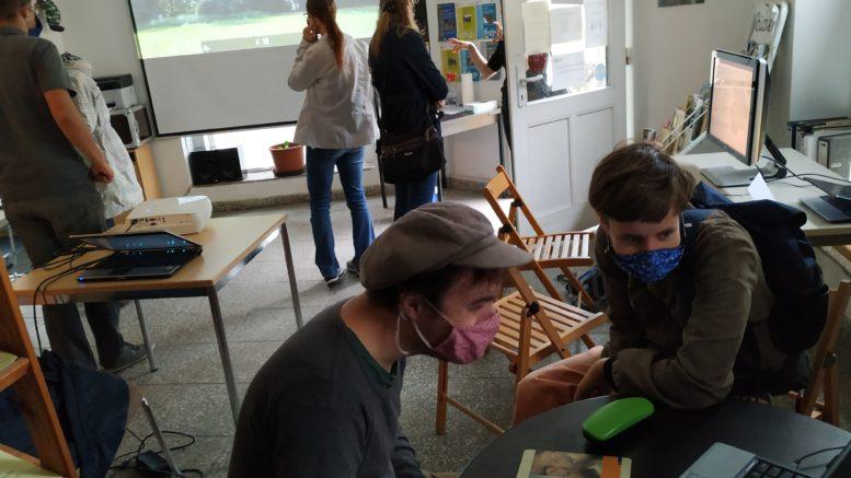 Besucherinnen und Besucher schauen sich Bilder über Leinwand und Monitor an.