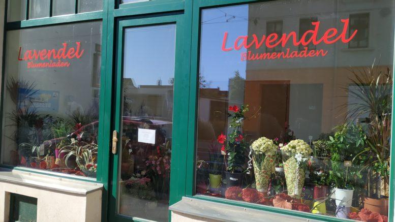 Außenansicht eines Blumengeschäftes mit zwei großen Schaufenstern und einer Glastür.