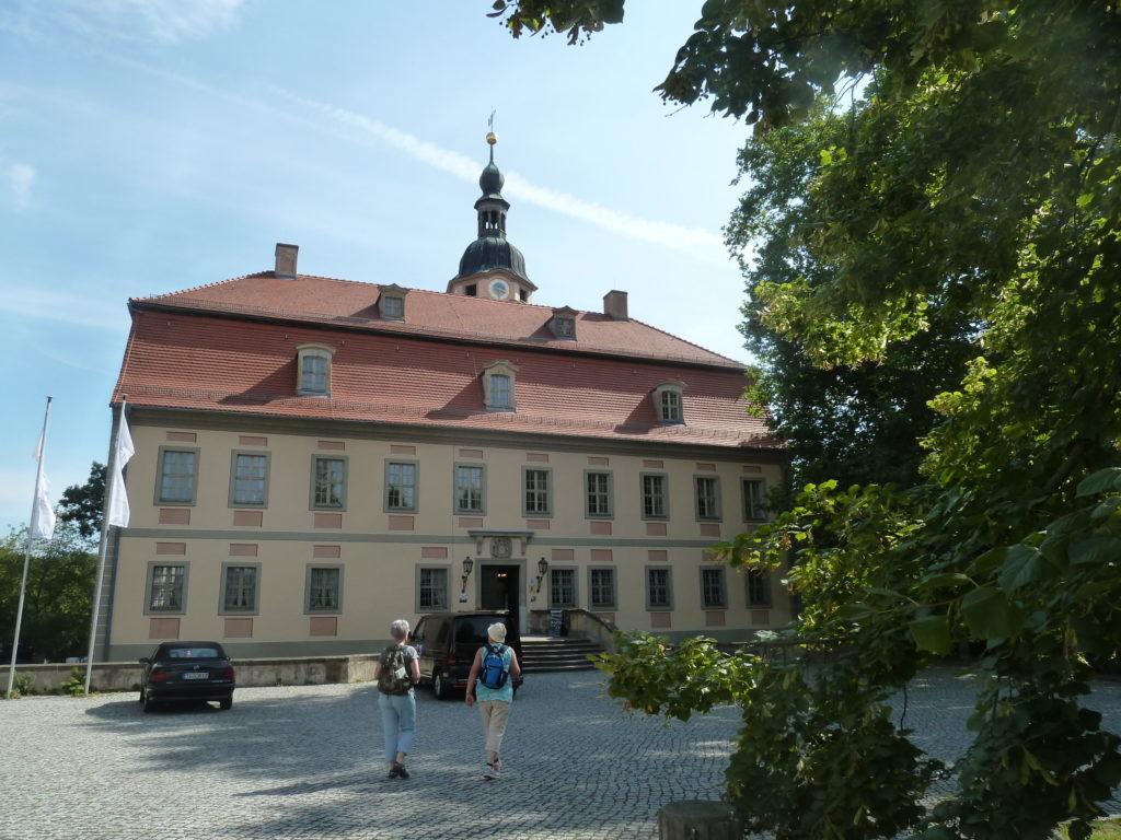 Das Schloss Machern, davor ein Auto und zwei Menschen die darauf zu gehen.