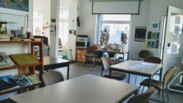 Innenraum des Leutzscher Stadtteilladens mit Tischen und Stühlen.