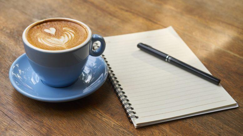 Eine Kaffeetasse und ein Schreibblock mit Stift auf Holzuntergrund.