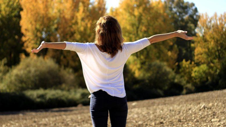 Frau im Freien, streckt Arme weit von sich, Bäume im Hintergrund.